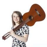El adolescente en vestido sostiene la guitarra en hombro en estudio Fotos de archivo