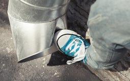 El adolescente en zapatillas de deporte azules golpea el tubo de drenaje con el pie, agresión Imagenes de archivo