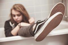 El adolescente en zapatillas de deporte negras se sienta en baño Fotos de archivo libres de regalías