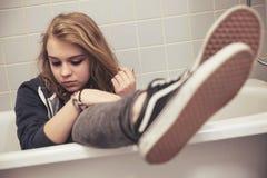 El adolescente en zapatillas de deporte negras se sienta en el baño, primer Imagenes de archivo