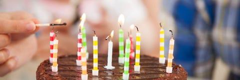 El adolescente enciende las velas en una torta de cumpleaños imagen de archivo