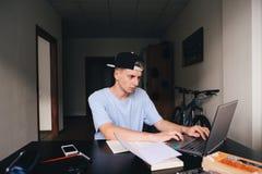 El adolescente encubierto está trabajando en un ordenador en su sitio Estudio en el país Imagen de archivo