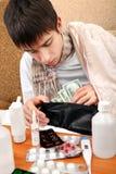 El adolescente enfermo comprueba la cartera Fotografía de archivo libre de regalías