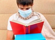 El adolescente enfermo leyó un libro Foto de archivo