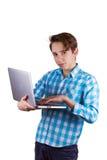 El adolescente es de trabajo o que juega en el ordenador portátil, aislado en blanco Fotografía de archivo libre de regalías