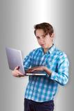 El adolescente es de trabajo o que juega en ordenador portátil Imagen de archivo