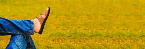 el adolescente es relajante en hierba con las piernas cruzadas en la rodilla en una foto feliz de la forma de vida Imagen de archivo libre de regalías
