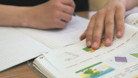El adolescente escribe el texto en cuaderno en la lección almacen de video