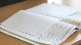 El adolescente escribe el texto en una hoja de papel blanca almacen de metraje de vídeo