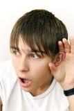 El adolescente escucha algo Fotos de archivo libres de regalías