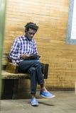El adolescente escucha la música mientras que espera en el statio del subterráneo Foto de archivo