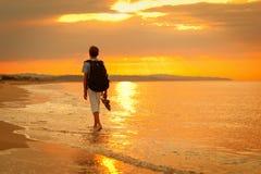 El adolescente está en la costa, puesta del sol Fotografía de archivo