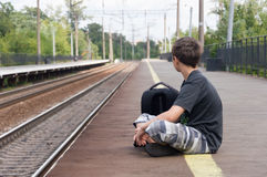 El adolescente está esperando un tren para colocar Imagenes de archivo