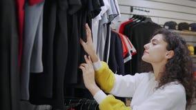 El adolescente está examinando las camisetas en tienda de la ropa de moda solamente metrajes