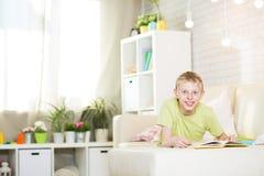 El adolescente está leyendo un libro Imagen de archivo