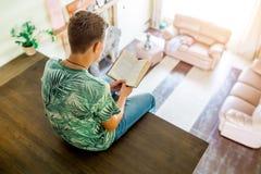 El adolescente está leyendo un libro, sentándose en la segunda planta de la casa Vista superior del cuarto Foco selectivo Fotos de archivo libres de regalías