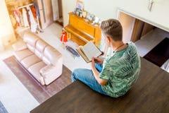El adolescente está leyendo un libro, sentándose en la segunda planta de la casa Vista superior del cuarto Foco selectivo Fotografía de archivo libre de regalías