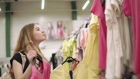 El adolescente está llevando a cabo el hambre dos con las camisetas en un pasillo de la tienda, decidiendo almacen de metraje de vídeo