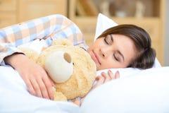 El adolescente está medio dormido con su oso de peluche Imagen de archivo
