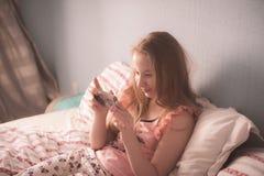 El adolescente está mintiendo en el sol inmorning y la mirada de la cama Imagen de archivo