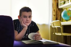 El adolescente está mintiendo en el sofá y está leyendo un libro Imagen de archivo libre de regalías