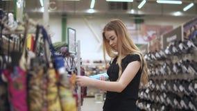 El adolescente está mirando el paraguas plegable en una tienda, girándolo en manos metrajes