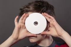 El adolescente está mirando a través del agujero de un disco blanco Fotos de archivo libres de regalías