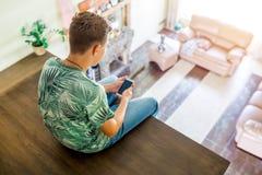 El adolescente está utilizando el teléfono celular, sentándose en la segunda planta de la casa Vista superior del cuarto Foco sel Imagen de archivo libre de regalías