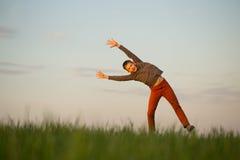 El adolescente está volando sobre el campo en la puesta del sol Imagenes de archivo