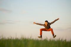 El adolescente está volando sobre el campo en la puesta del sol Fotografía de archivo