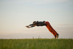 El adolescente está volando sobre el campo en la puesta del sol Imagen de archivo libre de regalías