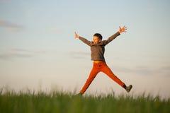 El adolescente está volando sobre el campo en la puesta del sol Foto de archivo libre de regalías