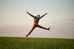 El adolescente está volando sobre el campo en la puesta del sol Fotos de archivo