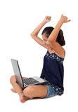 El adolescente exulta con los brazos para arriba con el ordenador portátil Imagen de archivo libre de regalías