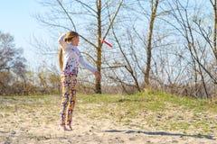 El adolescente feliz, blonde coge el disco del vuelo en un salto Fotos de archivo