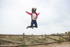 El adolescente feliz del tiro lleno que salta con las manos extendidas acerca al th Fotos de archivo
