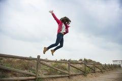 El adolescente feliz del tiro lleno que salta con las manos extendidas acerca al th Fotografía de archivo