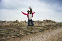 El adolescente feliz del tiro lleno que salta con las manos extendidas acerca al th Foto de archivo