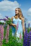 El adolescente feliz en campo del verano del lupine florece por completo Fotografía de archivo libre de regalías
