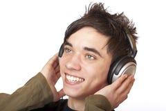El adolescente feliz escucha la música vía el auricular Fotografía de archivo