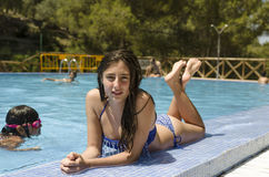 El adolescente feliz está mintiendo en una piscina, mirada en la cámara Fotos de archivo libres de regalías