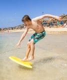 El adolescente feliz goza el practicar surf en las ondas Fotografía de archivo