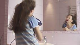 El adolescente feliz hermoso de la muchacha el cabello seco con el secador de pelo y canta y baila delante de un espejo en la acc metrajes