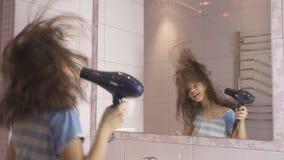 El adolescente feliz hermoso de la muchacha el cabello seco con el secador de pelo y canta y baila delante de un espejo en el cua Foto de archivo