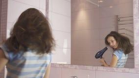El adolescente feliz hermoso de la muchacha el cabello seco con el secador de pelo y canta y baila delante de un espejo en el cua Imagen de archivo