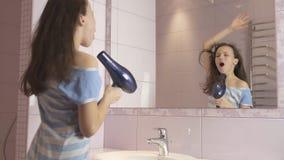 El adolescente feliz hermoso de la muchacha el cabello seco con el secador de pelo y canta y baila delante de un espejo en el cua Fotografía de archivo