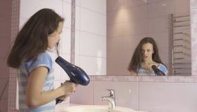 El adolescente feliz hermoso de la muchacha el cabello seco con el secador de pelo y canta y baila delante de un espejo en el cua Imagen de archivo libre de regalías