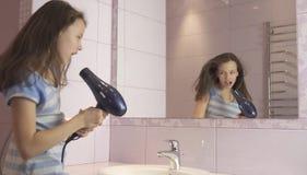 El adolescente feliz hermoso de la muchacha el cabello seco con el secador de pelo y canta y baila delante de un espejo en el cua Fotos de archivo