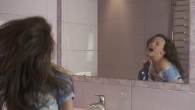 El adolescente feliz hermoso de la muchacha el cabello seco con el secador de pelo y canta y baila delante de un espejo en el cua almacen de video