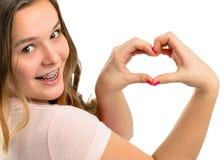 El adolescente feliz hermoso muestra el corazón del gesto Foto de archivo